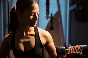 ダンベルを持ちトレーニングをする真剣な表情の20代女性の写真素材 [FYI02669067]
