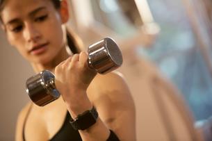 ダンベルを持ちトレーニングをする20代女性の写真素材 [FYI02669106]