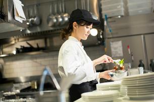 調理場で働く笑顔の20代女性の写真素材 [FYI02669127]