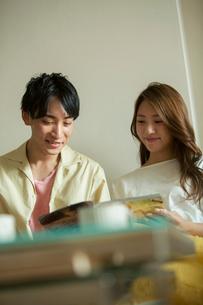 部屋で雑誌を読む笑顔の20代カップルの写真素材 [FYI02669134]