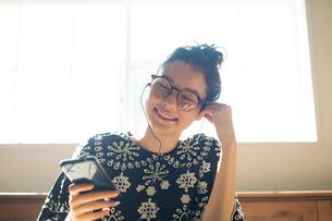 窓際に座りスマホを見る20代女性の写真素材 [FYI02669186]