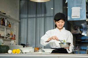 調理場で働く笑顔の20代女性の写真素材 [FYI02669208]