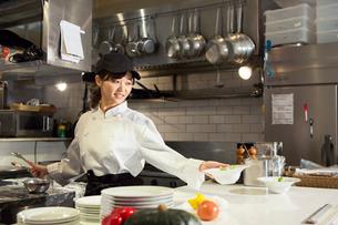 調理場で働く笑顔の20代女性の写真素材 [FYI02669209]