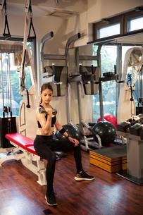 ダンベルを持ちトレーニングをする20代女性の写真素材 [FYI02669212]
