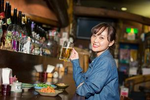 居酒屋で一人飲みを楽しむ20代女性の写真素材 [FYI02669218]