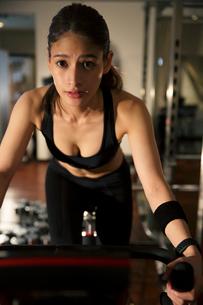 エアロバイクを漕ぐ20代女性の写真素材 [FYI02669235]