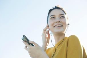 青空の下音楽を聴く20代女性の写真素材 [FYI02669261]