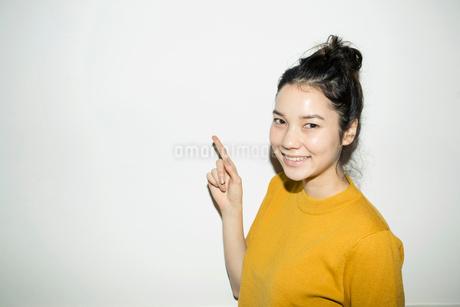 指差しをする笑顔の20代女性の写真素材 [FYI02669272]
