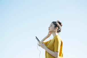 青空の下音楽を聴く20代女性の写真素材 [FYI02669280]