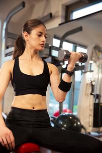 ダンベルを持ちトレーニングをする20代女性の写真素材 [FYI02669348]