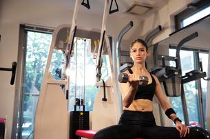 ダンベルを持ちトレーニングをする20代女性の写真素材 [FYI02669351]