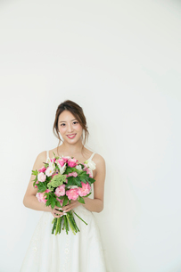 ブーケを持ちドレス姿で微笑む花嫁の写真素材 [FYI02669359]