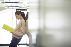 廊下でファイルを確認する20代女性の写真素材 [FYI02669360]