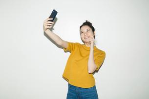 自撮りをする笑顔の20代女性のポートレートの写真素材 [FYI02669365]