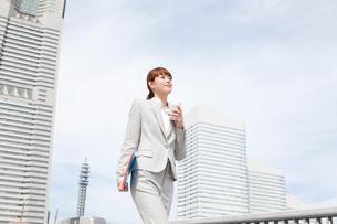 コーヒーカップを持ちながら歩くヤングビジネスウーマンの写真素材 [FYI02669382]