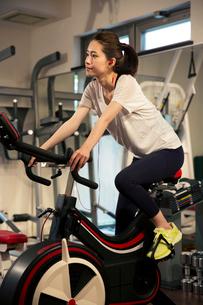音楽を聴きながらエアロバイクを漕ぐ20代女性の写真素材 [FYI02669391]