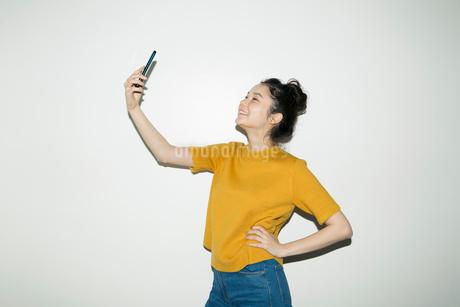 自撮りをする笑顔の20代女性のポートレートの写真素材 [FYI02669418]