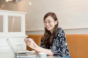 パソコンを見て単語帳を確認する20代女性の写真素材 [FYI02669423]