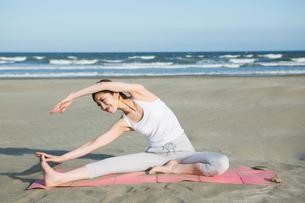 浜辺でヨガをする20代女性の写真素材 [FYI02669440]