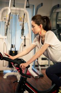 音楽を聴きながらエアロバイクを漕ぐ20代女性の写真素材 [FYI02669450]