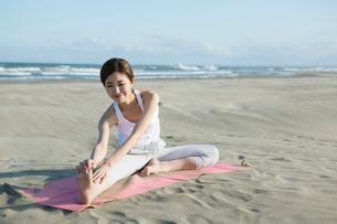 浜辺でヨガをする20代女性の写真素材 [FYI02669467]