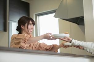 キッチンから料理を受け渡す20代女性の写真素材 [FYI02669476]