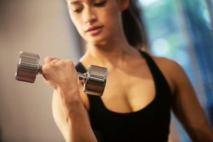 ダンベルを持ちトレーニングをする20代女性の写真素材 [FYI02669533]