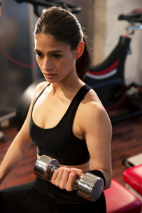 ダンベルを持ちトレーニングをする20代女性の写真素材 [FYI02669561]