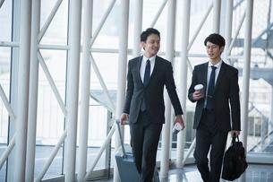 飲み物を持ち屋内を歩くスーツ姿の20代男性2人の写真素材 [FYI02669697]