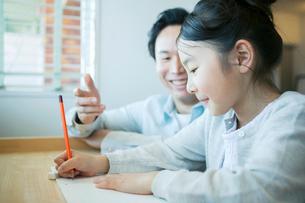 部屋で勉強を教えてもらう女の子の写真素材 [FYI02670610]
