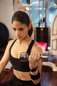ダンベルを持ちトレーニングをする20代女性の写真素材 [FYI02670652]