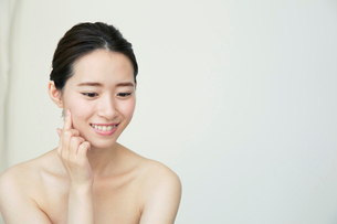 肌に手を当てて状態を確かめる笑顔の20代女性の写真素材 [FYI02670701]