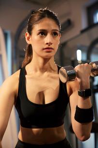 ダンベルを持ちトレーニングをする真剣な表情の20代女性の写真素材 [FYI02670753]