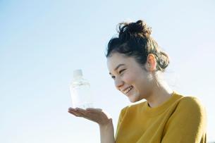 青空の下ペットボトルを手に乗せる20代女性の写真素材 [FYI02670936]