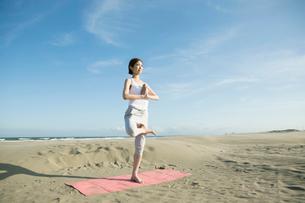 浜辺でヨガをする20代女性の写真素材 [FYI02671016]