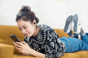 ソファに寝転びスマホを見る20代女性の写真素材 [FYI02671024]