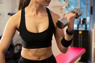 ダンベルを持ちトレーニングをする20代女性の写真素材 [FYI02671053]