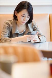 カフェでスマホを操作する笑顔の20代女子の写真素材 [FYI02671065]