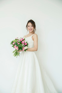 ブーケを持ちドレス姿で微笑む花嫁の写真素材 [FYI02671082]