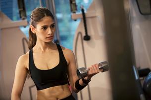 ダンベルを持ちトレーニングをする20代女性の写真素材 [FYI02671089]