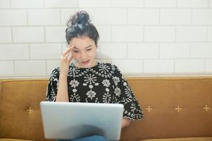 パソコンを見つめ悩む20代女性の写真素材 [FYI02671097]
