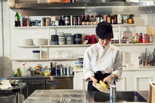 食器を洗う20代女性の写真素材 [FYI02671100]
