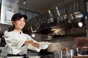 お皿を差し出す笑顔の20代女性の写真素材 [FYI02671126]