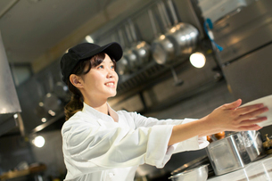 調理場で働く笑顔の20代女性の写真素材 [FYI02671133]