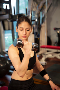 ダンベルを持ちトレーニングをする20代女性の写真素材 [FYI02671141]