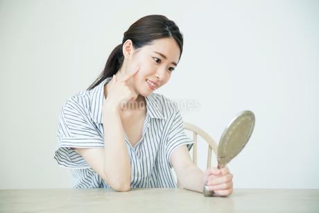 鏡を持ち肌に手を当て状態を確かめる20代女性の写真素材 [FYI02671159]