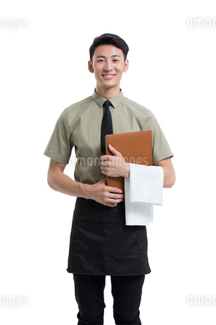 Young Chinese waiter holding a menuの写真素材 [FYI02672526]