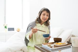 ベッドで食事をするシニア女性の写真素材 [FYI02673067]