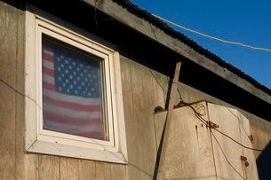 家の窓に掲げられた星条旗の写真素材 [FYI02673137]