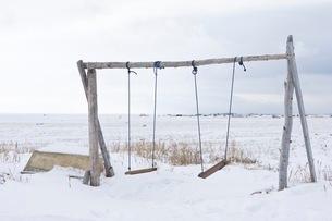雪に覆われた地に立つブランコの写真素材 [FYI02673141]